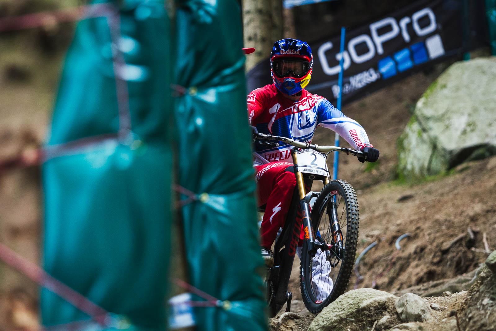 Aaron Gwin, reconociendo algunos tramos del circuito y viendo como los demás riders descienden sobre las piedras.