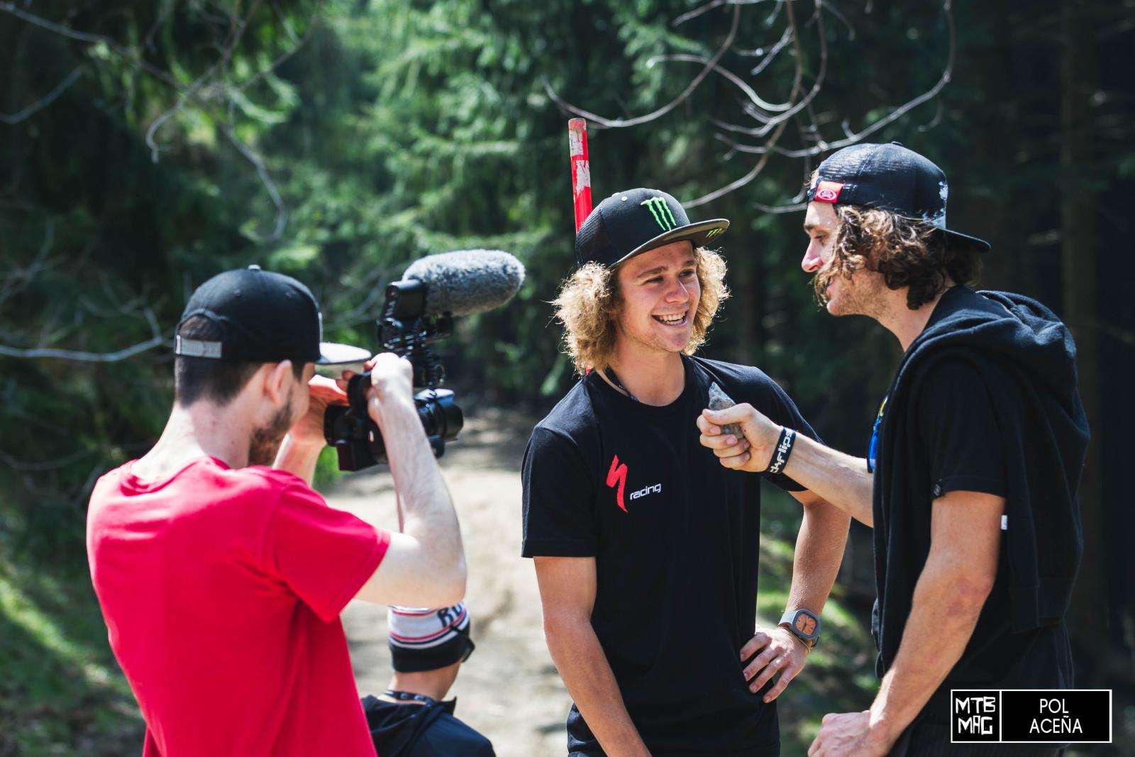 Wyn Masters es toda una personalidad en el mundo del descenso, no solo compite, sino que también se dedica a entrevistar a todos los pilotos para su propio programa. Aquí está entrevistando a Troy Brosnan en la rampa del primer road-gap del circuito.