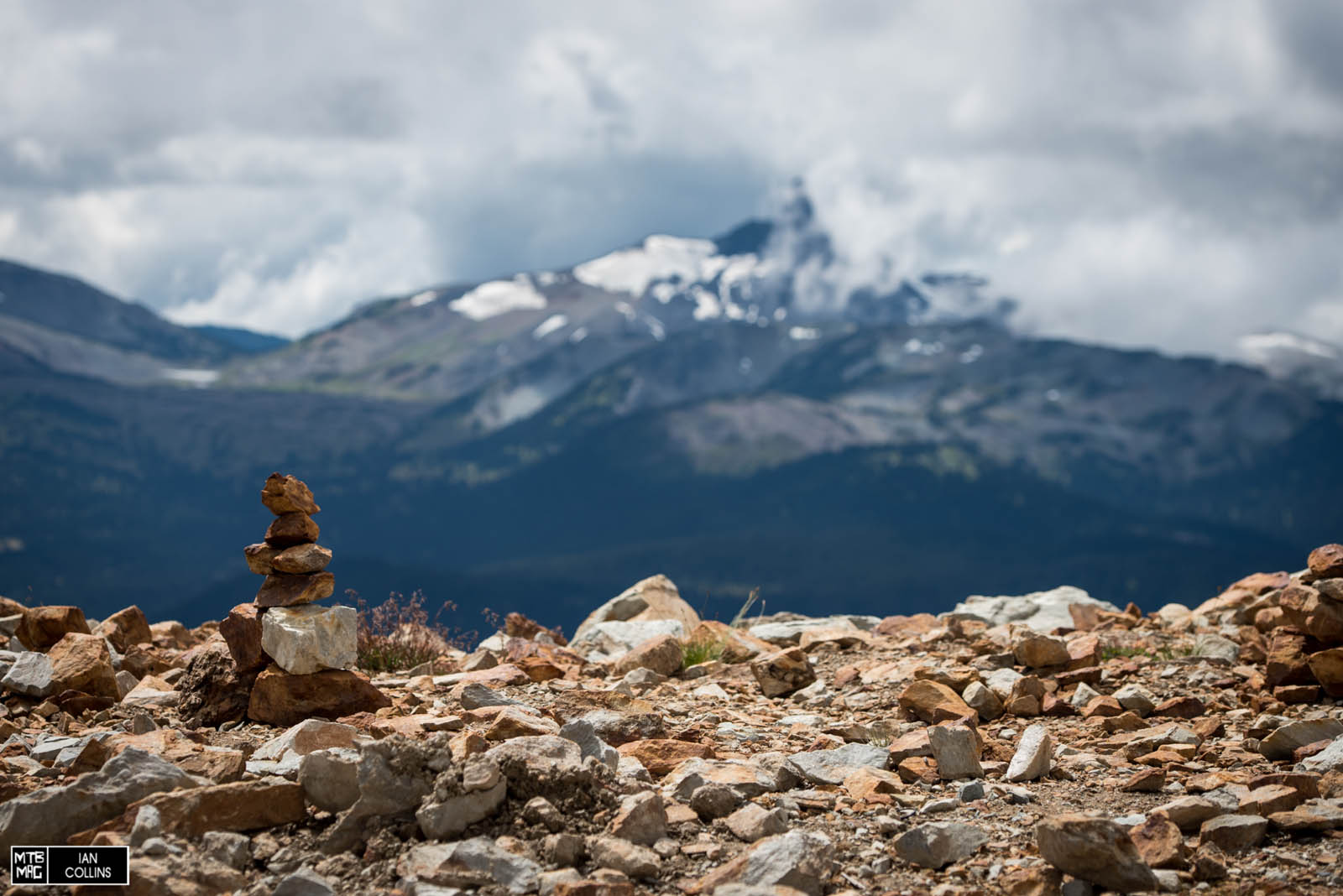 Rock piles with black tusk obscured by clouds in the background.